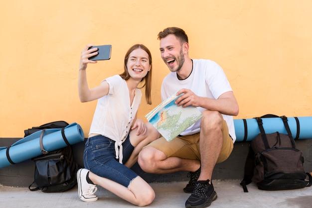 Улыбающаяся пара туристов, делающая селфи вместе