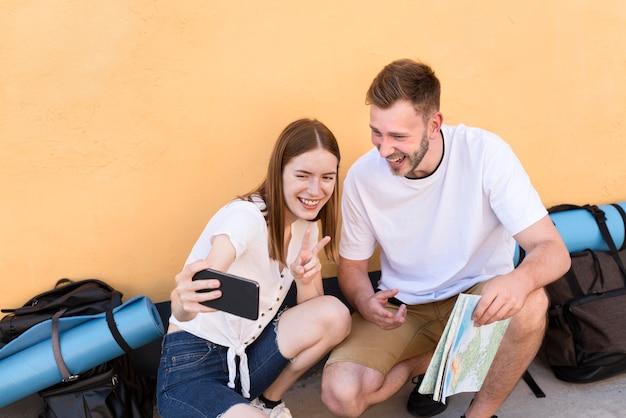 Улыбающаяся пара туристов, делающая селфи с телефоном