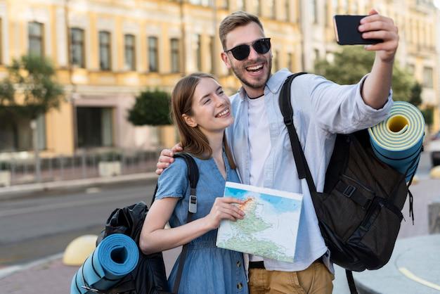 Улыбающаяся пара туристов, делающая селфи с рюкзаками