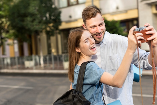Smiley tourist couple taking selfie with camera