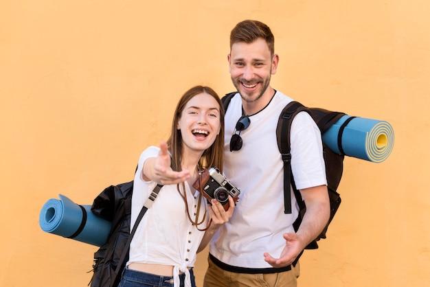 スマイリー観光カップルのバックパックとカメラ