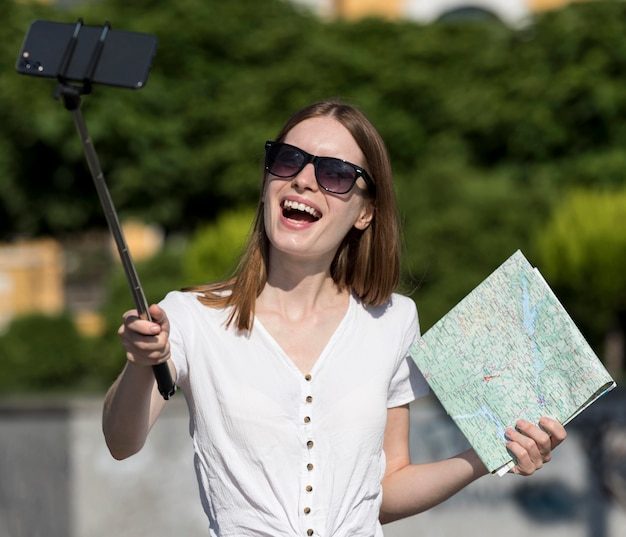 Smiley tourist woman holding map and taking selfie