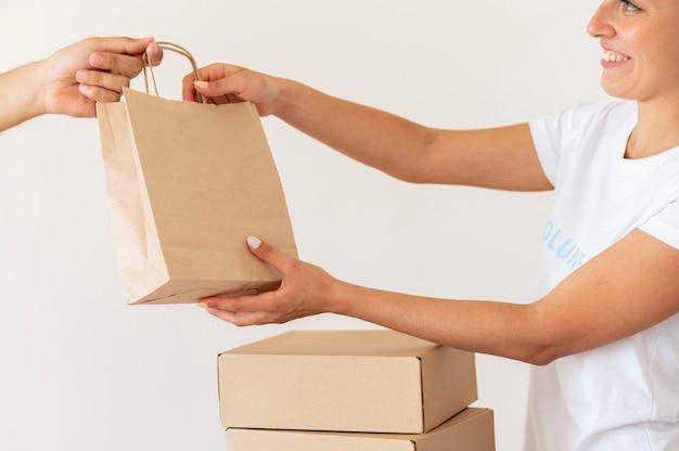 Смайлик-волонтер вручает сумку с пожертвованиями на еду