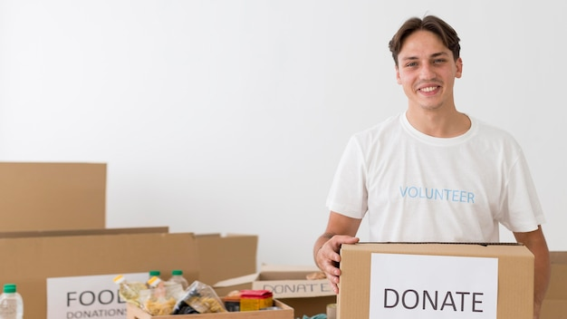 Smiley volunteer holding a donate box with copy space