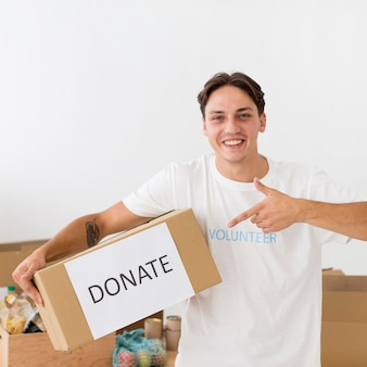 Smiley volunteer pointing to a donate box