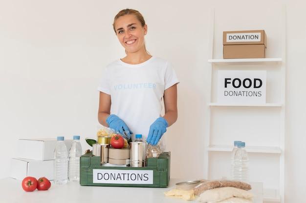 Volontario di smiley con guanti che maneggia la scatola delle donazioni di cibo
