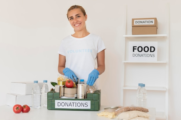 食品寄付の箱を扱う手袋をしたスマイリーボランティア