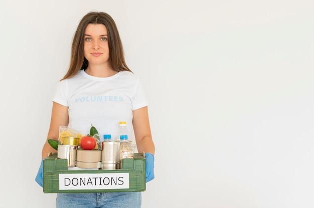 コピースペースのある食糧寄付の箱を保持している手袋をしたスマイリーボランティア