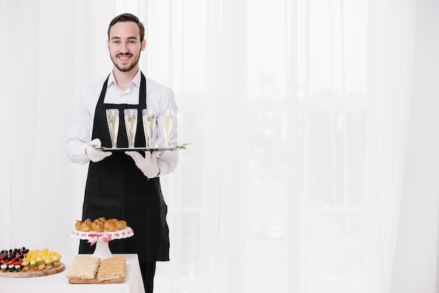 Smiley waiter holding glasses with copy space