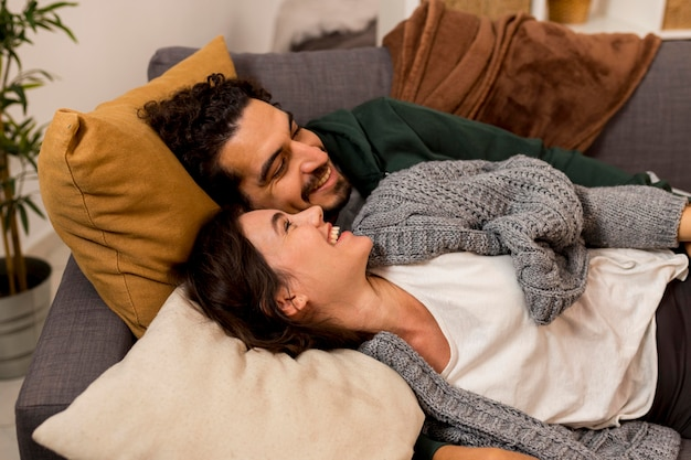 Смайлик жена и муж лежат на диване