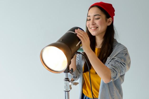 Smiley woman adjusting light