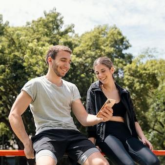 운동하는 동안 야외에서 스마트 폰으로 웃는 여자와 남자