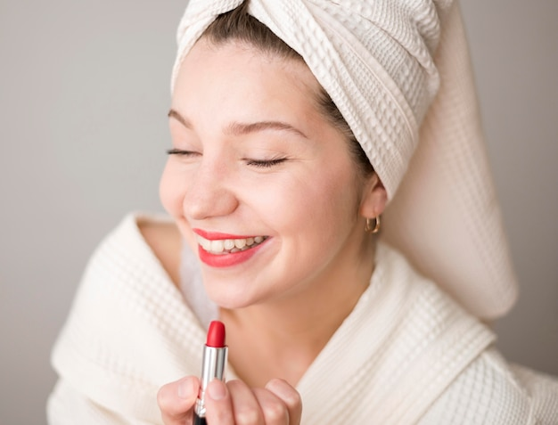 Smiley woman applying lipstick