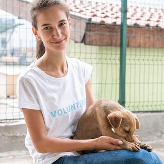 입양을 위해 개를 들고 동물 보호소에서 웃는 여자