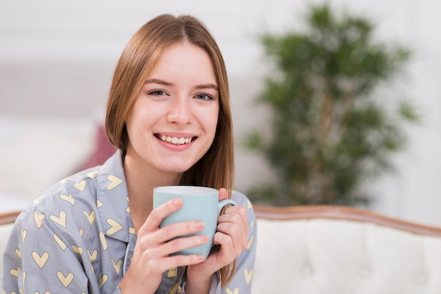 Улыбающаяся женщина дома пьет чай