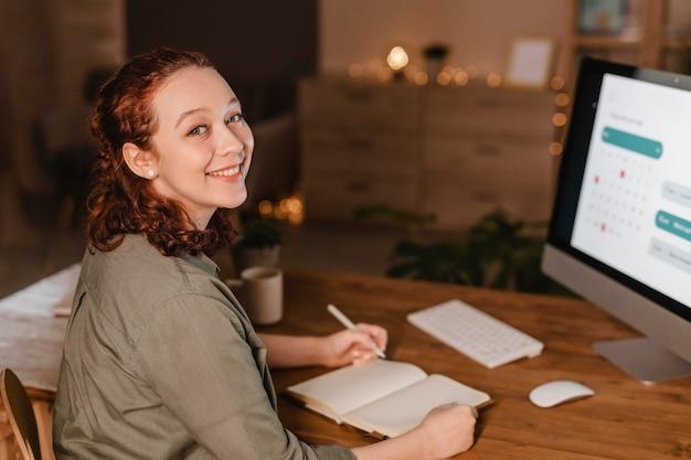 彼女のコンピューターを使用して自宅でスマイリー女性