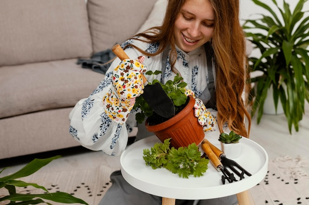 식물과 원예 도구의 냄비와 집에서 웃는 여자