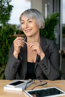 Улыбающаяся женщина за столом держит очки
