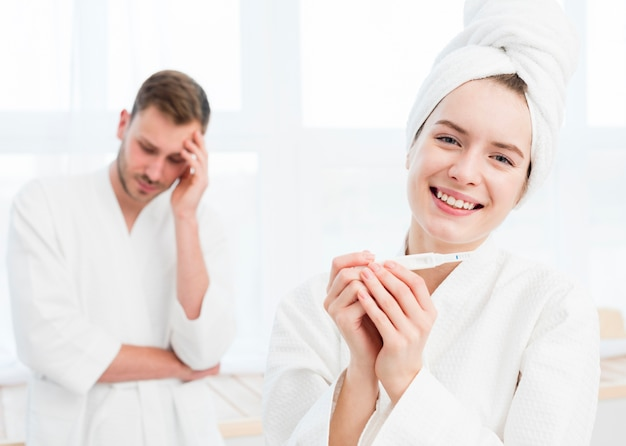 Smiley woman in bathrobe holding bathrobe with concerned man