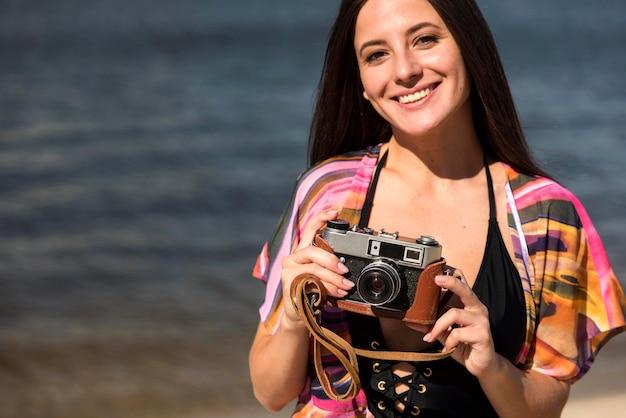 Donna sorridente in spiaggia tenendo la fotocamera