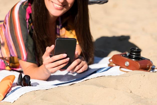 Donna sorridente in spiaggia tenendo lo smartphone