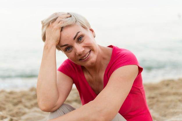 Donna di smiley sulla posa della spiaggia
