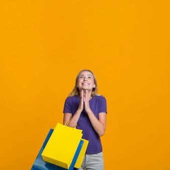 Donna sorridente che è felice della sua baldoria di acquisto e che osserva in su con lo spazio della copia