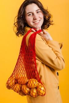 Smiley woman carrying lemons