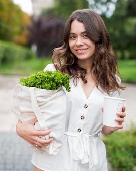 Смайлик женщина, несущая органические покупки