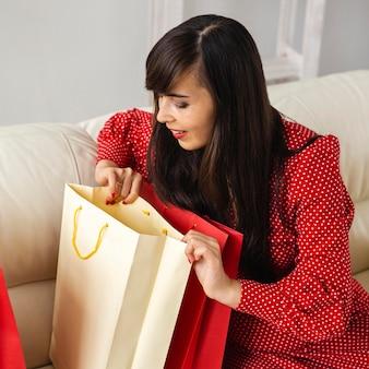 판매 쇼핑하는 동안받은 가방을 확인하는 웃는 여자