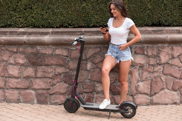 Smiley woman checking her smartphone while on electric scooter