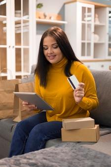 スマイリー女性がサイバー月曜日に新しい購入のタブレットをチェック