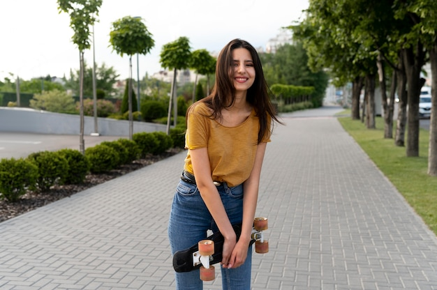 Smiley woman in the city holding skateboard