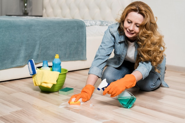 Smiley woman cleaning the floors