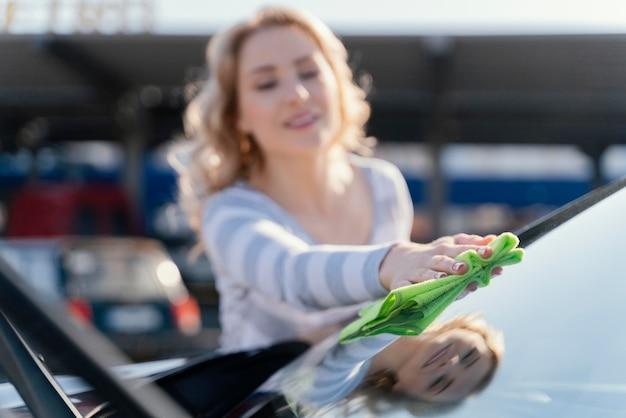 Смайлик женщина, чистящая свою машину на улице