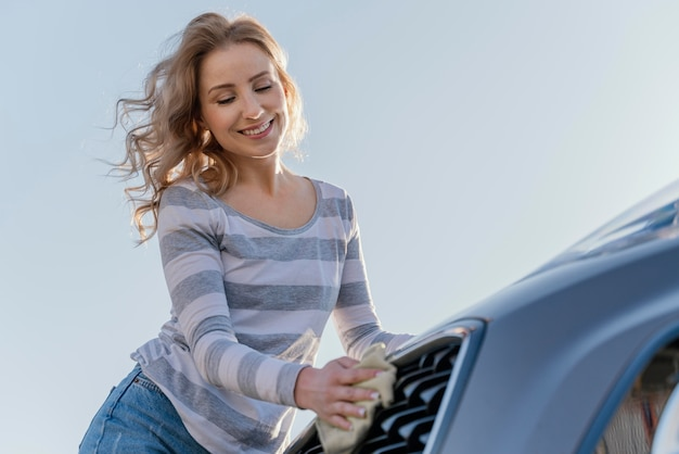 Smiley woman cleaning her car outside