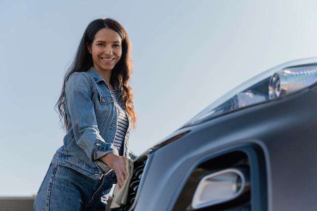 Donna sorridente che pulisce la sua macchina fuori