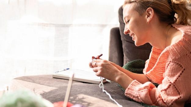 Smiley woman crocheting indoors