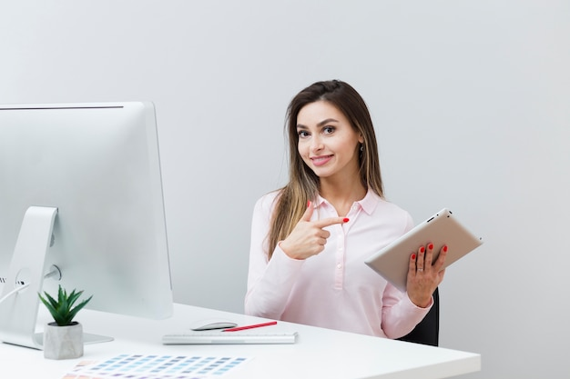 Smiley woman at desk pointing at tablet