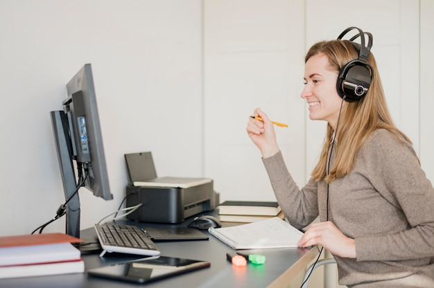 Smiley woman at desk wearing headphones and having an online class