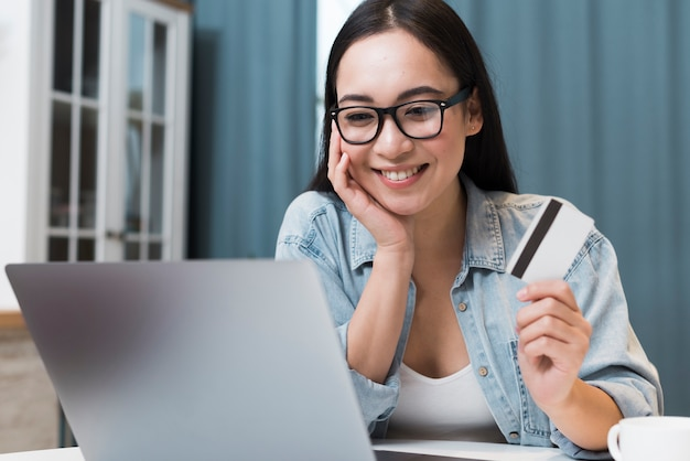 Smiley woman at desk with credit card and laptop