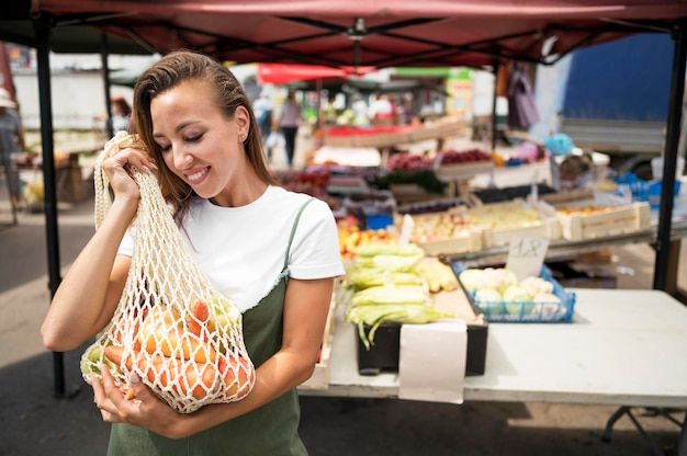 Smiley woman doing groceries shopping with copy space