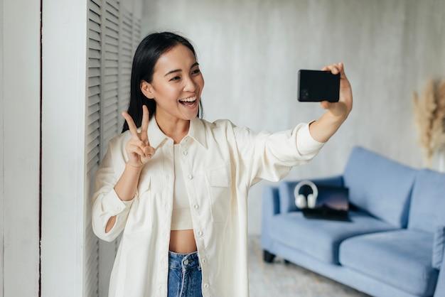 Donna sorridente che fa un vlog con il suo telefono