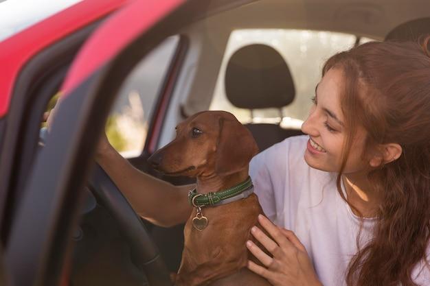 Donna sorridente che guida con il cane da vicino