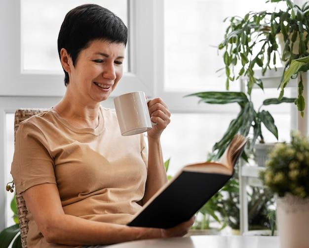 Смайлик женщина, наслаждаясь книгой в помещении с кружкой