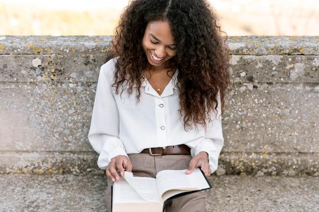 Smiley woman enjoying a book outdoors