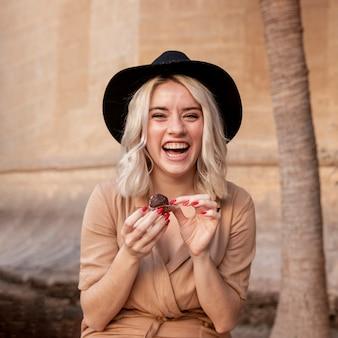 Donna di smiley che gode di un cupcake