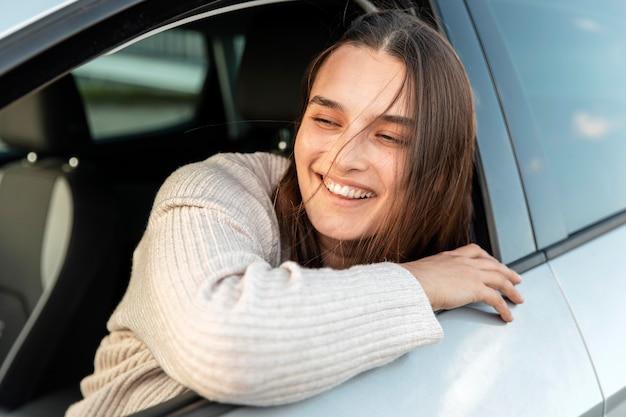 Donna sorridente che gode di un viaggio su strada nella sua auto