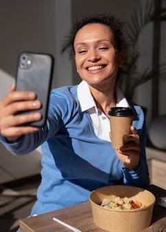 Smiley woman enjoying takeaway food and taking selfie