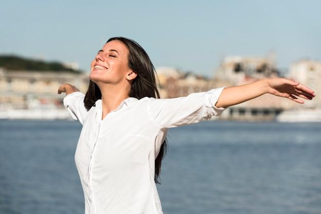 ビーチのそよ風を楽しむスマイリー女性
